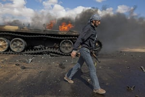 Sean Smith in Libya: 20 March: A rebel soldier walks past destroyed tank