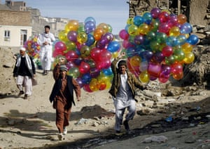 Spring festivals: Afghans carry balloons to sell as they walk towards the Sakhi Shrine