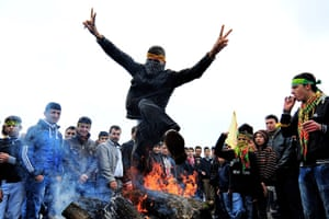 Spring festivals: A Turkish Kurd jumps over a fire during a gathering to celebrate Nowruz