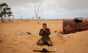 A Libyan rebel prays next to his gun on the outskirts of Ajdabiya