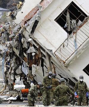Japan salvage: Japanese soldiers remove debris near damaged buildings in Onagawa