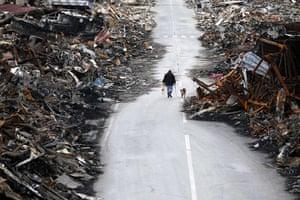 Japan salvage: A man walks with his dog in Kesennuma