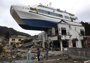 Japan salvage: A boat sits on top of a building in Otsuchi