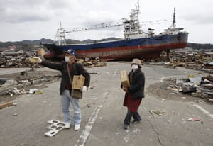 Japan salvage: Residents carry boxes of food in front of a fishing trawler in Kesennuma