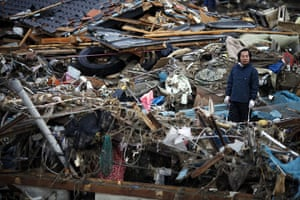 Japan salvage: A man inspects the damage as he tries to retrieve belongings in Otsuchi