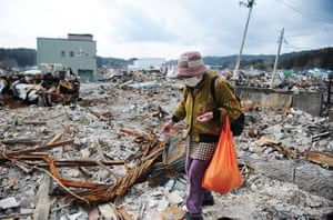Japan salvage: A woman lingers at the site her home was once located in Iwate