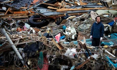 A man inspects the damage as he tries to retrieve belongings from a destroyed house in Otsuchi