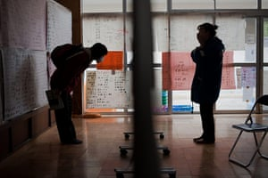 Japan aftermath: People read messages displayed on the wall of a relief centre