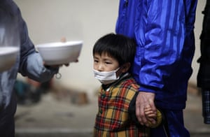 Japan aftermath: A boy waits for food at an evacuation centre in Otsuchi, Iwate Prefecture