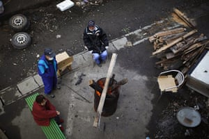 Japan : People sit next to a fire in an area destroyed by the tsunami in Kamaishi