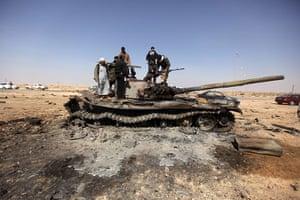Ajdabiya seized by rebels: Libyan rebels celebrate on a destroyed tank in Ajdabiya