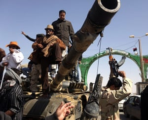 Ajdabiya seized by rebels: Libyan rebels celebrate on a tank destroyed by the coalition