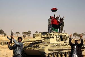Ajdabiya seized by rebels: Libyan rebels hold up the old Libyan flag on a destroyed tank