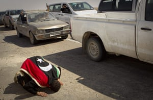 Ajdabiya seized by rebels: A rebel, draped in the old Libyan flag, prays at the entrance to the city