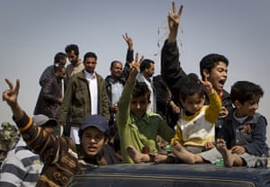 Ajdabiya seized by rebels: Libyan children celebrate on top of a car after rebels took the city