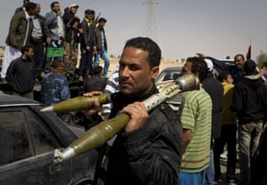 Ajdabiya seized by rebels: A Libyan rebel carries rocket propelled grenades after taking the city