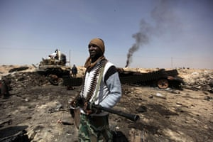 Ajdabiya seized by rebels: A Libyan rebel on a coalition air strikes site in the strategic oil town