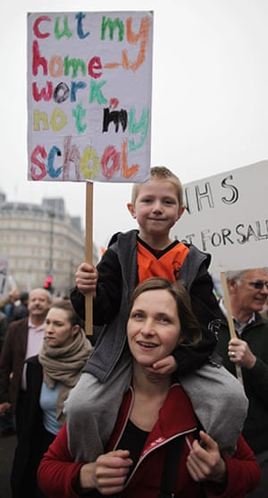 Protest against cuts: A boy holds a placard in protest at government cuts