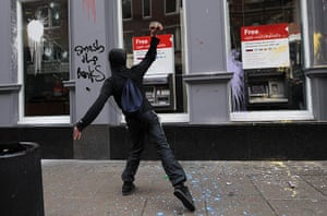London Protest: A protestor attempts to smash the window of a HSBC bank branch with a brick
