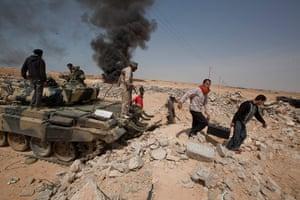Sean Smith in Libya: Rebel supporters scavenge for scrap from a Gaddifi tank in Adjabaya