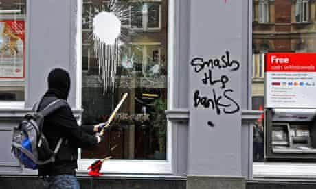 A protester smashes a window at a HSBC