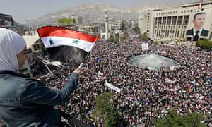 Syrian pro-government demonstrators gather in a central square in Damascus to support Assad