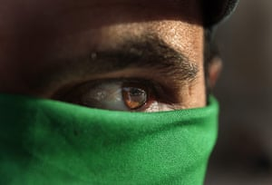 24 hours: A pro Gadaffi supporter wears a green over his face