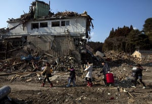 From the agencies: a family salvage their belongings in Rikuzentakata