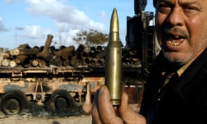 A man holds up a round of ammunition at the road between Benghazi and Ajdabiyah