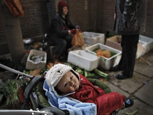 from the agencies: A baby sits in a buggy at a vegetable stall
