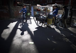 from the agencies: Locals buy breakfast from a bicycle food stall behind an office building