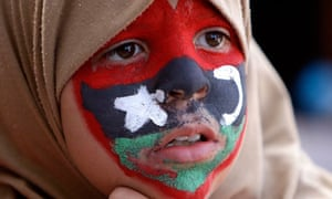 A young anti-Gaddafi protester with the old Libyan flag painted on her face.