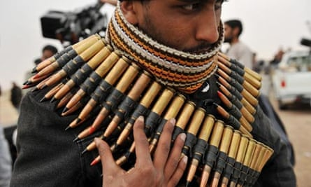 A Libyan rebel fighter wraps himself in a machine gun ammunition belt