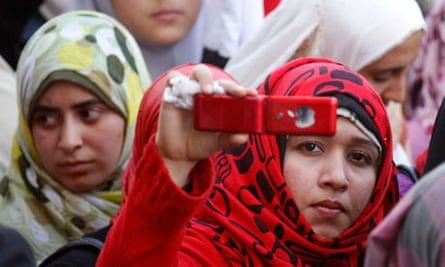 A girl takes a photo with her mobile in cairo
