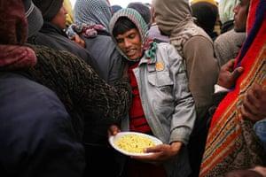 Libya Ras Jdir: A Bangladeshi man walks through a line with his food at a camp in Ras Jdir