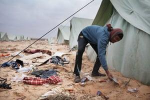 Libya Ras Jdir: A Bangladeshi man tries to improve the support of his his tent at Ras Jdir