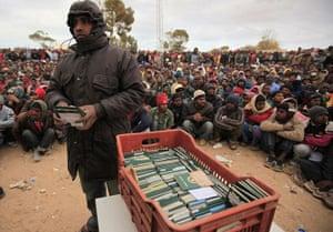 Libya Ras Jdir: A Bangladeshi evacuee holds his compatriots' passports at a refugee camp