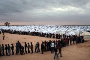 Libya Ras Jdir: Men who recently crossed into Tunisia from Libya wait in line