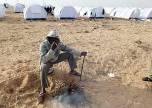 Libya Ras Jdir: A Malian refugee sits by a campfire at the UNHCR refugee camp at Ras Jdir