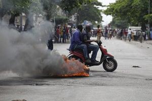 Ivory Coast violence: Men ride a moped past burning debris shortly after civilians were shot at