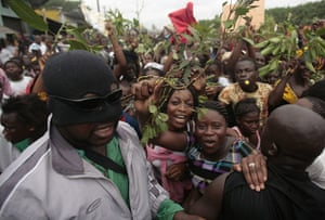 Ivory Coast violence: A man in a balaclava provides security at a rally of supporters of Ouattara