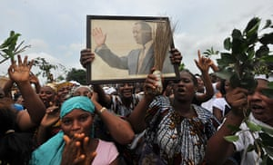 Ivory Coast violence: Women hold a portrait of presidential claimant  Alassane Ouattara