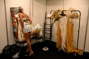 from the agencies : A woman looks in the mirror as prepares for Sunday's carnival parade
