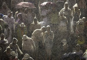 from the agencies : Spectators watch the Grande Rio samba school parade in the rain