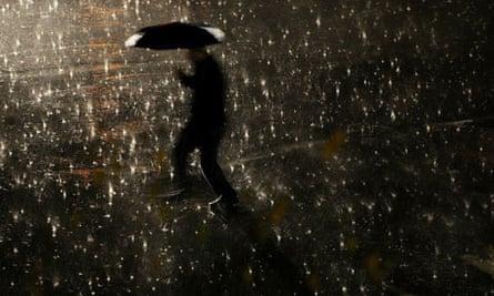 A man walks with his umbrella