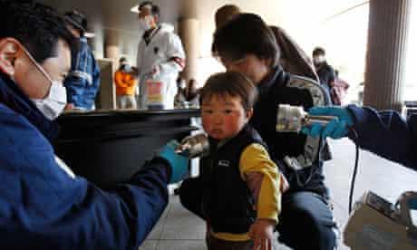 A boy is screened for radiation contamination at Fukushima