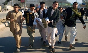 Afghans carrying a man wounded in the outbreak of violence at Mazar-e-Sharif