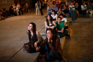 24 hours in pictures: People watch on a screen during a speech in Malaga