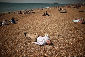 24 hours in pictures: A man enjoys a lie down in the sunshine on the beach, Brighton, UK