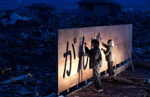24 hours in pictures: Tsunami survivors draw the words in a billboard, Japan